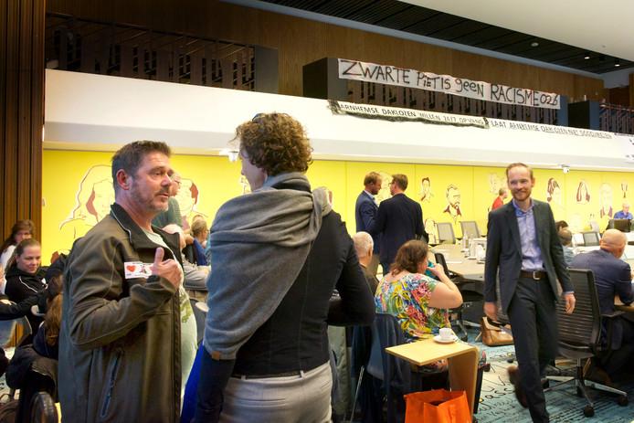 Arnhemmer Rob Garritsen (l) is aanwezig in de vergadering van de gemeenteraad van Arnhem om van zijn sympathie voor de klassieke figuur van Zwarte Piet te getuigen. Anders dan door critici beweerd, is die volgens hem niuet racistisch.