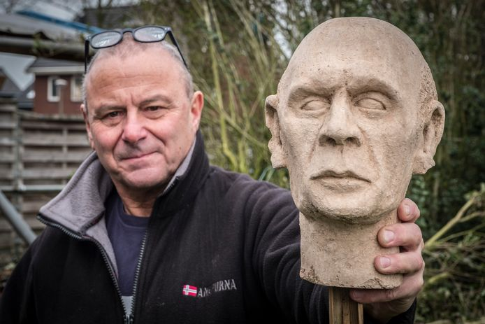 Hans van Alem met de kunstkop die hij in de tuin vond.
