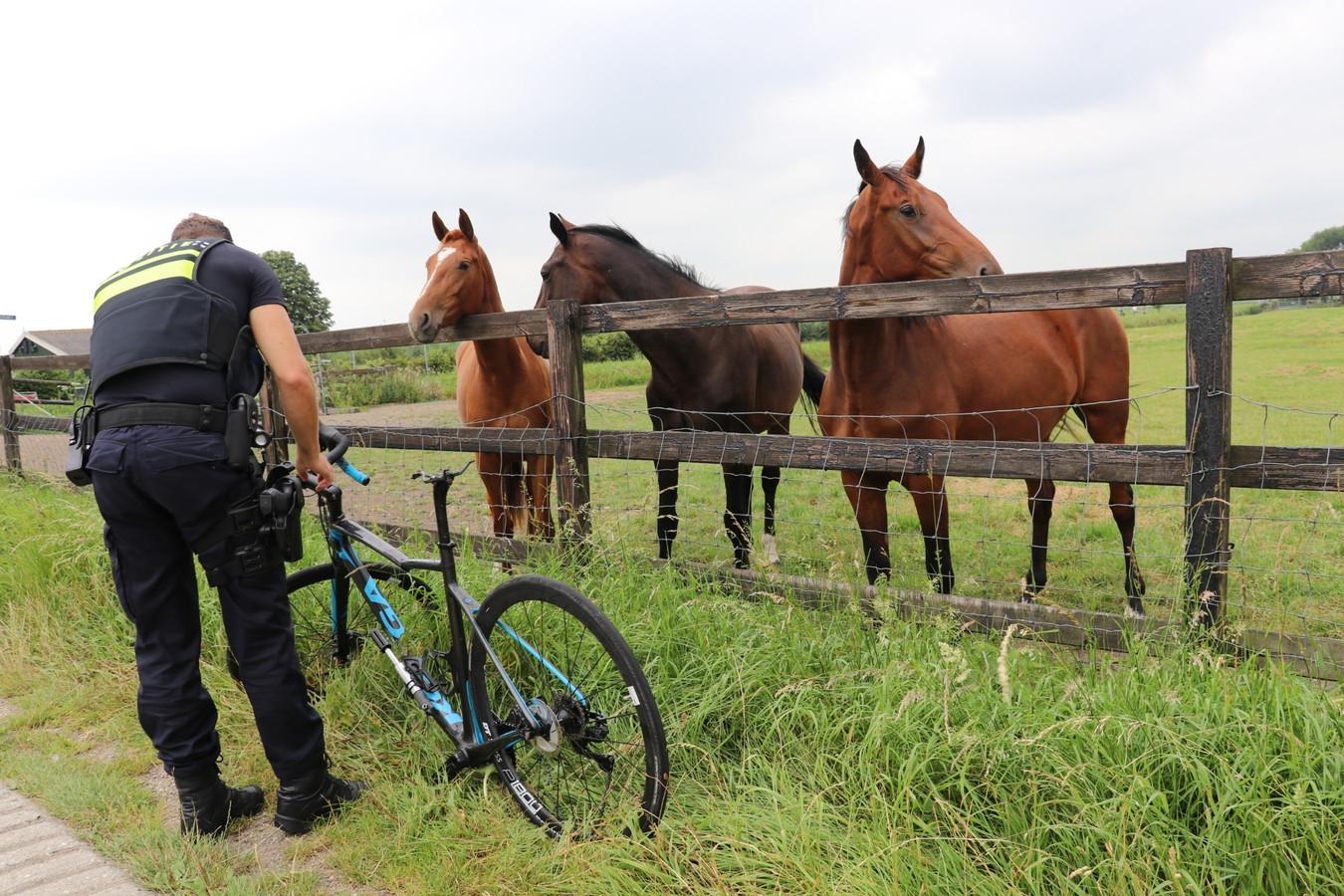 Een agent inspecteert de fiets van de onfortuinlijke wielrenner.