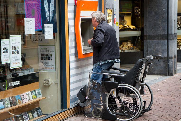 Een man staat op uit zijn rolstoel om geld te pinnen bij een pinautomaat van in Arnhem. Pinautomaten zijn voor veel gehandicapten moeilijk toegankelijk.  Beeld Hollandse Hoogte