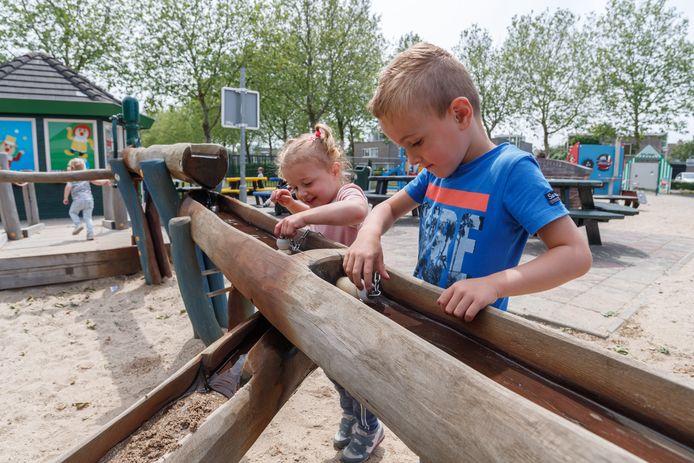 Kinderen bij een waterpomp op een natuurspeelplek in Etten-Leur. Iets dergelijk moet ook komen in Ellecom.