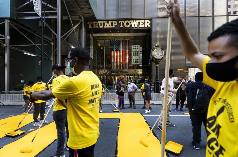 Black Lives Matter-activisten brengen een gigantische BLM-tekening aan voor de deur van de Trump Tower in New York. Beeld EPA