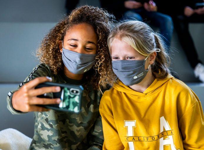 Archiefbeeld: leerlingen van een middelbare school maken een selfie met hun mondkapje op tijdens de pauze.