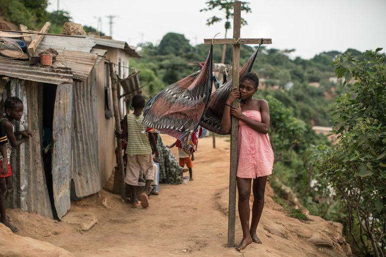 Een meisje staat bij de was in een arme buurt in Cabinda, de regio waar de helft van de Angolese olie vandaan komt. Beeld rv