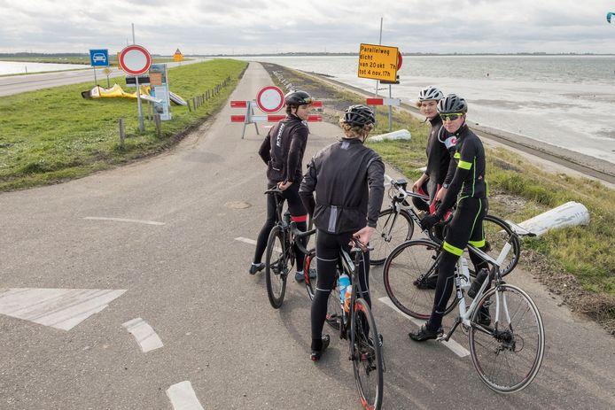 Een groepje Vlaamse jongens op weg naar België staat vertwijfeld voor de afgesloten weg.  Moeten ze doorfietsen of helemaal terugkeren en via Tholen en Brabant naar huis?