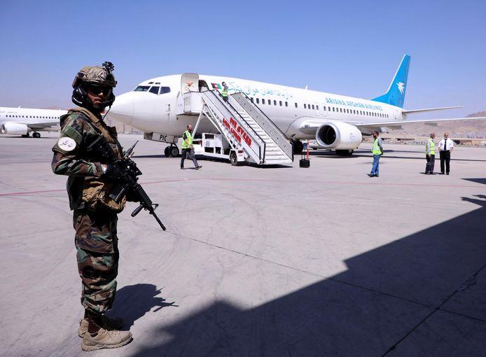 Een lid van de taliban staat op wacht bij een vliegtuig dat is geland op de luchthaven van Kaboel.