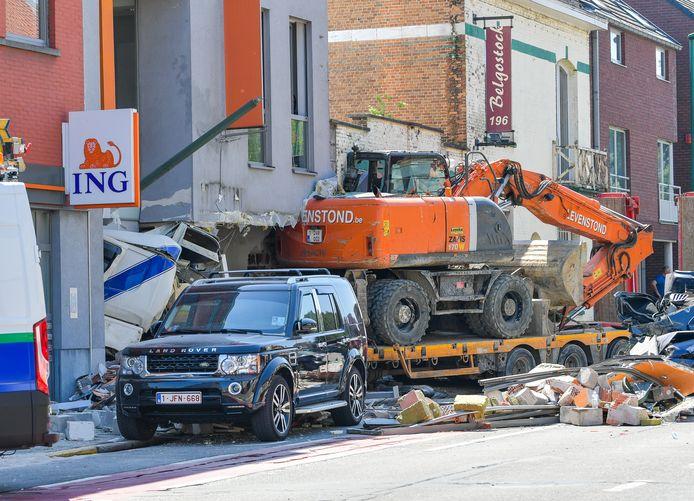 De vrachtwagen, met een graafmachine op de oplegger, boort zich tot slot in een ING-filiaal. De schade is amper te overzien.