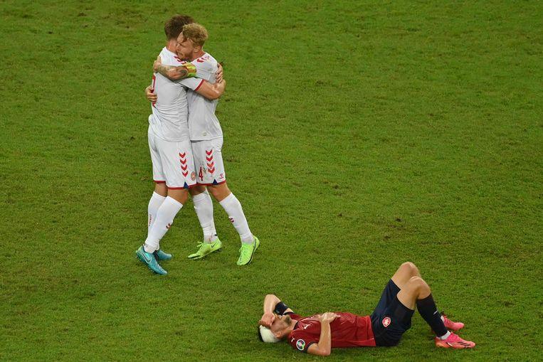 Joachim Andersen en Simon Kjaer omhelzen elkaar na het fluitsignaal terwijl de Tsjechische middenvelder Tomas Soucek verslagen op de grond ligt.  Beeld AFP
