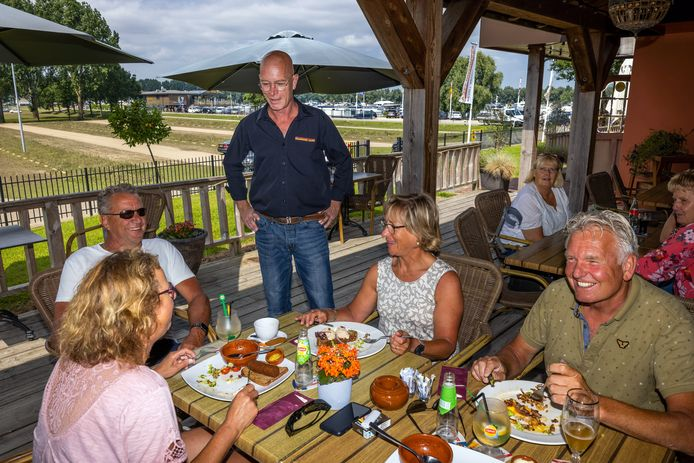 Martin van den Broek van Brandend Zand aan tafel bij Marjo en Henk Embregts (rechts) en Jan en Jolanda Verbruggen. Begin deze week stond recreatiegebied de Zandmeren nog helemaal onder water.