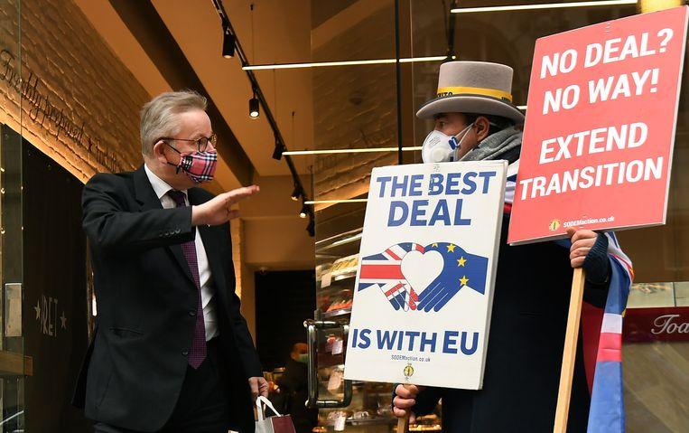 Michael Gove (links), de rechterhand van de Britse premier Boris Johnson, wordt geconfronteerd met een pro-EU-actievoerder in Londen. Beeld EPA