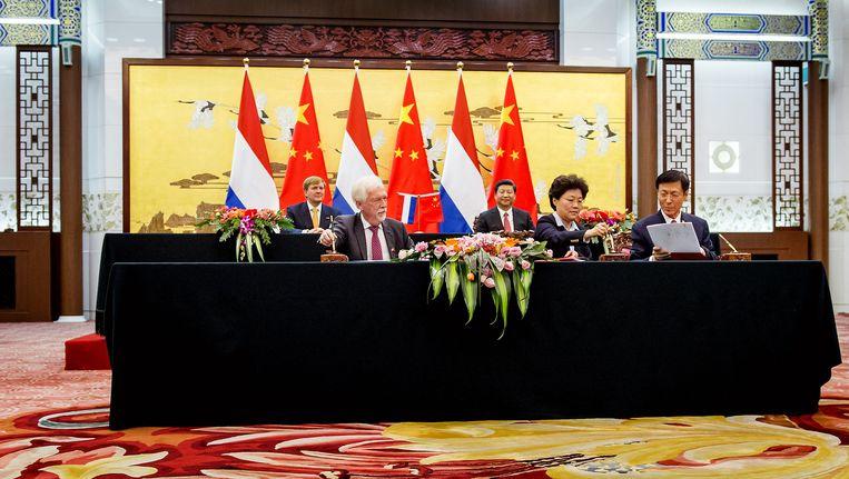 Onder toeziend oog van koning Willem-Alexander en president Xi Jinping tekent Poppema in Peking de overeenkomst. Beeld ANP