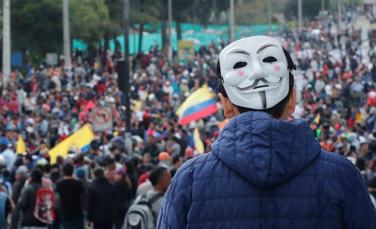 Een man met een Guy Fawkes-masker sluit zich aan bij de demonstratie.