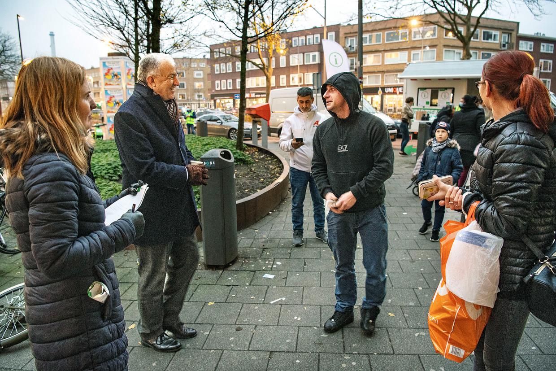 Burgemeester Ahmed Aboutaleb praat met een Poolse bewoner van Carnisse. Links Ewelina, die vanuit de gemeente contact legt met arbeidsmigranten. Beeld Guus Dubbelman / de Volkskrant