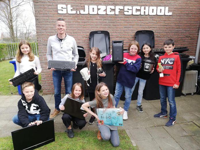 De winnaars van de E-waste Race, leerlingen van basisschool Sint Jozef uit Nieuw Namen, tussen een paar van de ingezamelde elektronische apparaten.