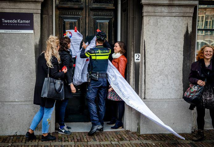 Tijdens een actie tegen het eigen risico in de zorg, hangen demonstranten een kamermotie en een lijst met namen van ondertekenaars van een petitie op aan de deur van de Stadhouderskamer.
