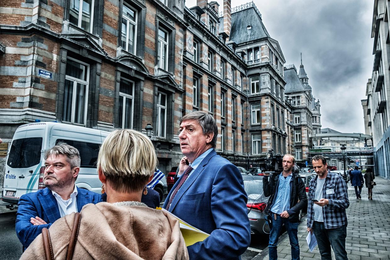 Vlaams minister-president Jan Jambon (N-VA) staat buiten bij het Vlaams Parlement, dat net ontruimd is na een bommelding. Beeld Tim Dirven