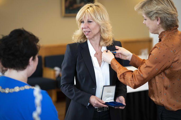 Burgemeester Sharon Dijksma van Utrecht overhandigde Claudia de Breij haar lintje, dat hier wordt opgespeld door De Breij's partner. Beeld ANP