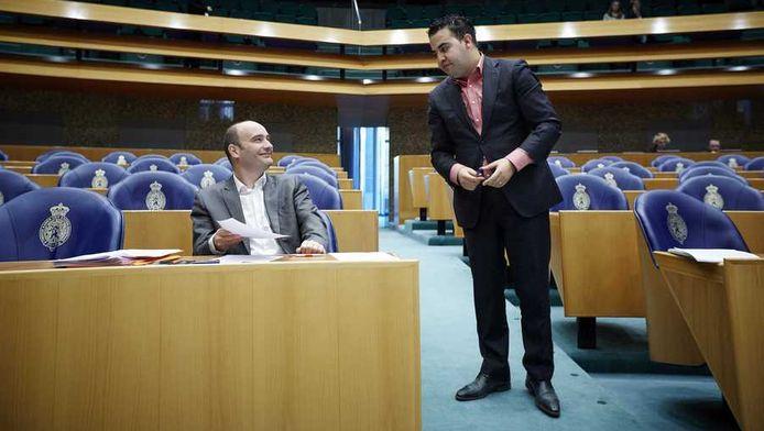 PvdA'er Mohandis (rechts) maakt een praatje met SP'er Van Dijk tijdens het debat over het sociaal leenstelsel in de Tweede Kamer.
