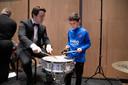 Een slagwerker van het Nijmeegs Studentenorkest laat een scholier zien hoe hij moet trommelen.