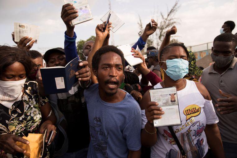 Honderden Haitianen verzamelen zich voor de Amerikaanse ambassade in Port-au-Prince, met het verzoek om een visum om het land te kunnen verlaten na de moord op de president. Beeld EPA