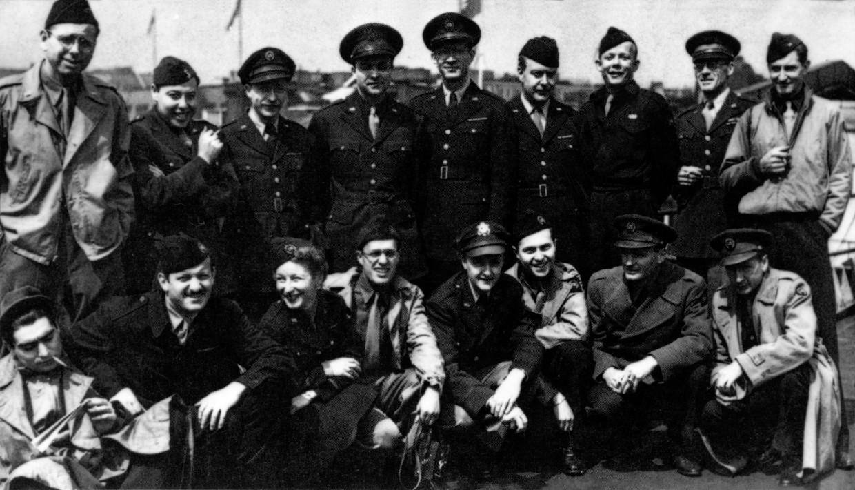 De D-day-ploeg van 'Time Magazine' met militairen op de foto. Fotograaf Robert Capa zit vooraan links (met sigaret).