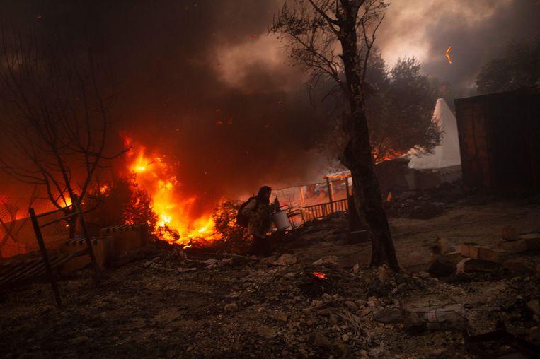 Een vrouw ontvlucht de brand in het opvangcentrum Moria in september vorig jaar. Beeld AFP