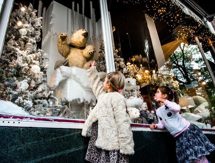 Kinderen bekijken de kerstetalage van een winkel in Rotterdam.