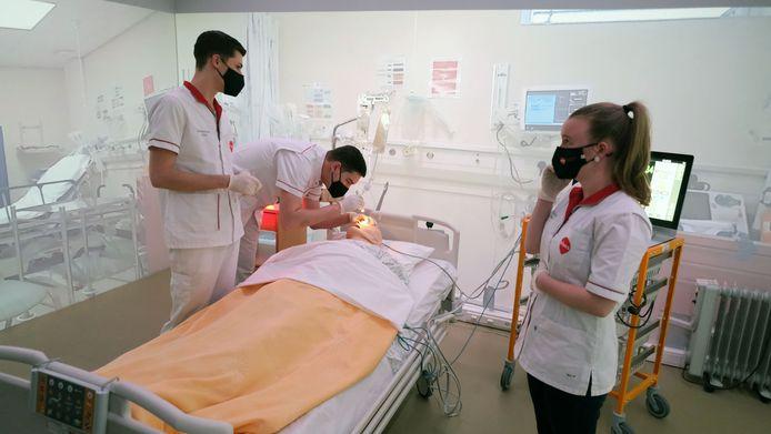 Student Laurens Dekiere komt er ook bij, om de pupillen van de patiënt te checken.
