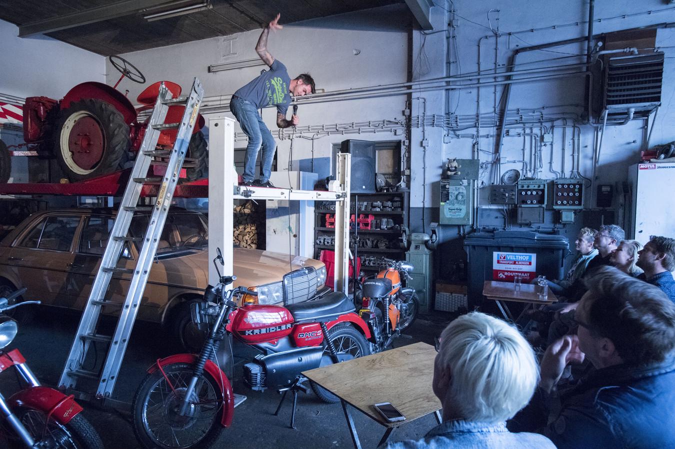 Cabaretier Emiel van der Logt treedt op in een oude tractorgarage, tijdens Comedy Express Albergen.