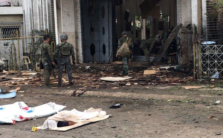 Filipijnse soldaten verzamelen bewijs bij een kerk in Jolo waar bij een IS-aanslag zeker 21 mensen zijn gedood.  Beeld EPA