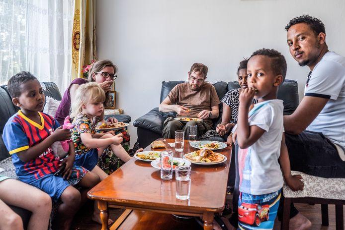 De Haagse en Eritrese families genieten samen van injera, hartige pannenkoekjes.