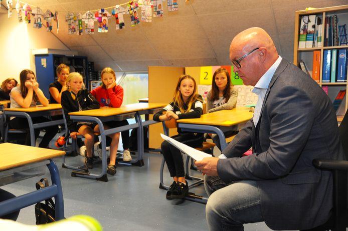 FOTO De Veerse wethouder Marcel Steketee leest voor in groep 8 van basisschool 't Klinket in Koudekerke terwijl Sofie, Marit, Vivian, Josephine en de andere kinderen luisteren naar het verhaal.
