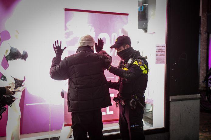 De politie controleert een demonstrant in Alphen bij een protest tegen de avondklok.