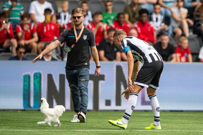 Heracles-captain Dario van den Buijs probeert de kip van het kunstgras te krijgen.