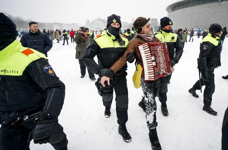 De politie houdt een man aan op het Museumplein die demonstreert tegen het coronabeleid. Beeld ANP