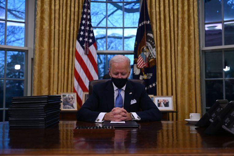 De Amerikaanse president Joe Biden in het Oval Office, kort nadat hij op 20 januari het Witte Huis had betrokken na zijn beëdiging. Hij tekende onmiddellijk een stapel decreten om maatregelen van Trump ongedaan te maken. Beeld AFP