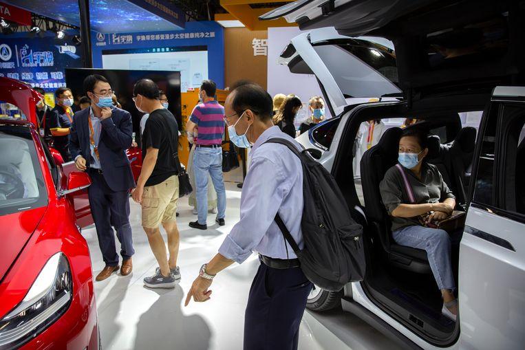 Bezoekers bekijken auto's van Tesla op een autobeurs in Beijing.  Beeld AP
