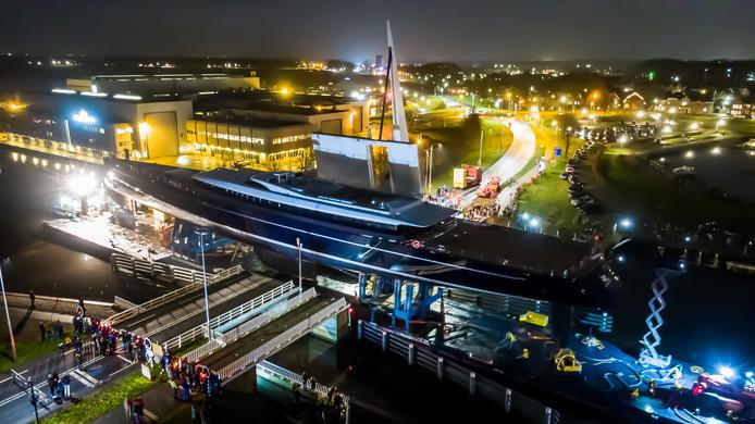 Het 81 meter lange zeiljacht passeert op pontons de Vollenhoverbrug. Op de achtergrond de werf waar het schip werd gebouwd.