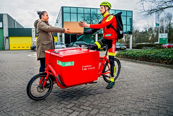 Fietskoerier Dennis haalt in Rotterdam een pakketje op bij een klant.