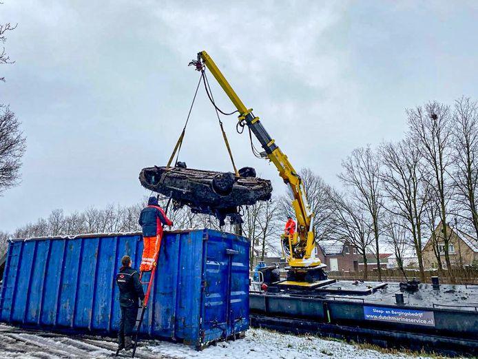Een van de twee auto's wordt uit het kanaal getakeld en in de container geplaatst in Helmond.
