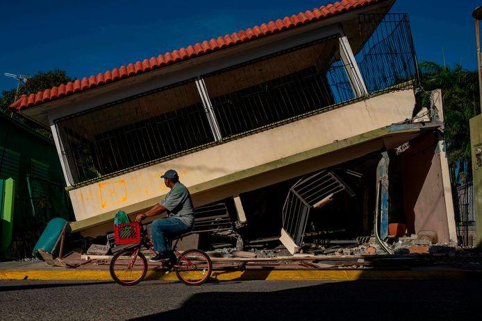 Een man rijdt voorbij een ingestort huis in Guanica, Puerto Rico (15/01/2020)