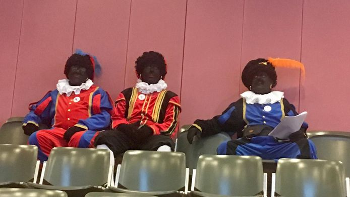 Zwarte Pieten op de tribune tijdens de raadsvergadering.