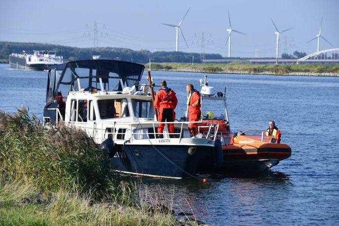 De motorjacht zit vast tegen de wal van het kanaal.