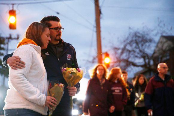 Een koppel brengt bloemen naar de synagoge om de elf doden te eren.