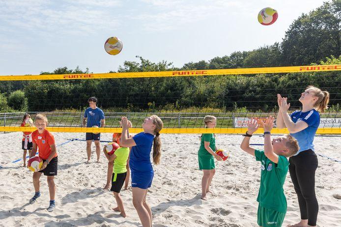 Leden van Volleybalclub Zwolle begeleiden de kinderen tijdens hun clinic. Basketballers van Landstede Hammers gingen de volleyballers al voor.