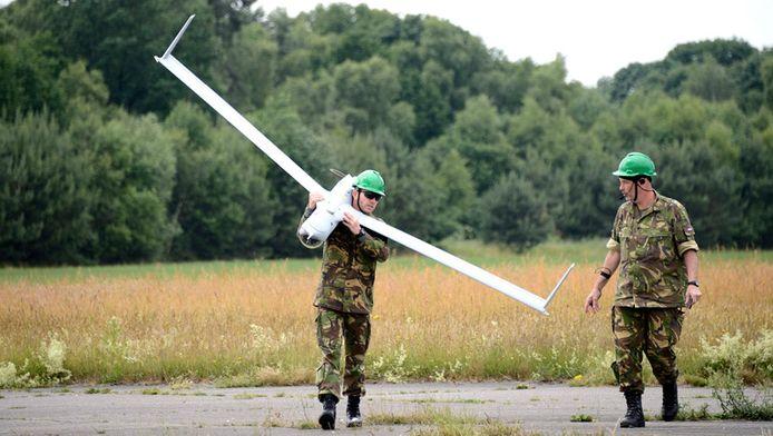 Een medewerker van Defensie loopt met een drone, een onbemand vliegtuigje dat vanaf 5 kilometer hoogte foto's of video's van de grond kan maken en meteen naar een grondstation kan sturen.
