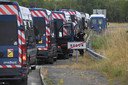 """TOPSHOT - French gendarmes stand on a road, near Redon, north-western France, on June 19, 2021, as they intervene to prevent an illegal rave party, which began during the night of June 18 to June 19, 2021. - Five gendarmes were injured during the intervention to disperse an illegal rave party in Redon (Ille-et-Vilaine) and a young participant """"of 22 years old lost a hand"""", announced on June 19, 2021 morning the prefect of Ille-et-Vilaine Emmanuel Berthier. """"The police has been confronted with violent individuals who refuse to leave the premises for several hours,"""" he said on June 19, 2021. (Photo by LOIC VENANCE / AFP)"""