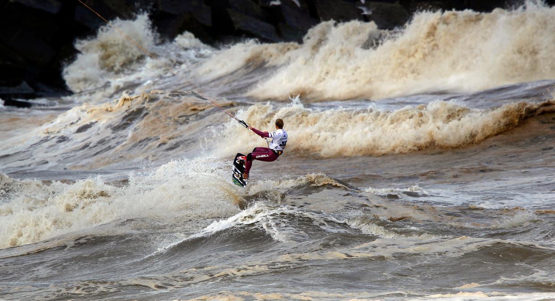 Een freestyler in actie tijdens de World Cup Kitesurfen. Lezer Frank Braakman vond zingeving in het kitesurfen.