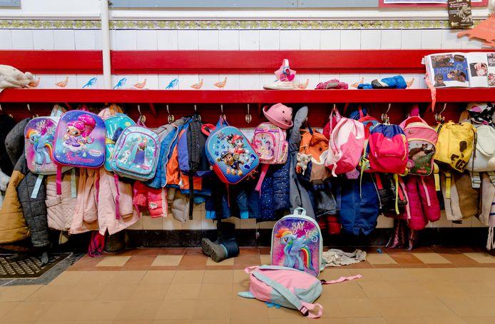Gang met tassen en jassen aan een kapstok op een basisschool.