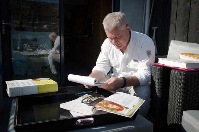 Marcel Voskens zoekt recepten uit voor zijn kookproject.